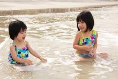 Los niños gozan de ondas en la playa Fotografía de archivo libre de regalías