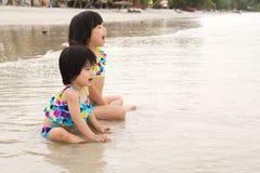 Los niños gozan de ondas en la playa Foto de archivo libre de regalías