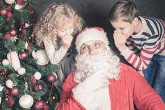 Los niños hablan con Santa Claus sobre el wishlist, regalos, noche de la Navidad Fotos de archivo