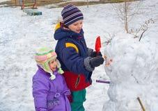 Los niños hacen el muñeco de nieve Fotografía de archivo libre de regalías
