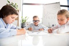 Los niños implicados están trabajando en oficina Imagen de archivo