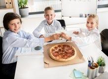 Los niños inteligentes alegres están almorzando Imágenes de archivo libres de regalías