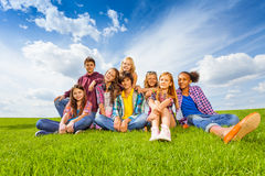 Los niños internacionales felices se sientan en prado verde Fotografía de archivo libre de regalías