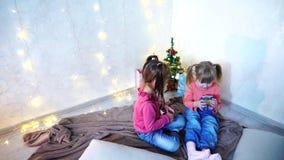 Los niños jovenes activos de muchachas ríen y engañan alrededor, sentándose en piso y en la manta, contra el fondo de la pared co metrajes