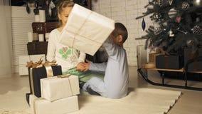 Los niños jovenes en pijamas miran regalos de Navidad debajo del árbol en la cámara lenta metrajes