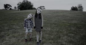 Los niños jovenes que llevan las máscaras blancas de un Halloween se colocan espeluznantemente y asustadizo almacen de metraje de vídeo