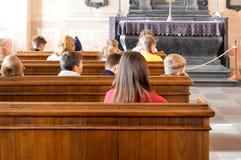 Los niños jovenes se sientan en los bancos de madera para el servicio en Christian Orthodox Catholic Church, el templo imagenes de archivo