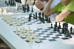 Los niños juegan a ajedrez al aire libre foto de archivo