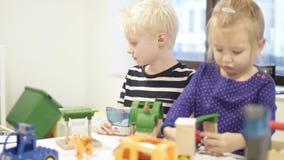 Los niños juegan al constructor de madera en la tabla en la sala de juegos almacen de video