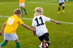 Los niños juegan al partido de fútbol Partido al aire libre del torneo del fútbol de los niños en campo de hierba imagen de archivo