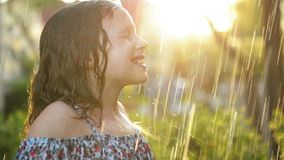 Los niños juegan en lluvia del verano o Gotas de lluvia de cogida de la niña debajo de la ducha pesada Ca?da metrajes