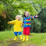 Los niños juegan en lluvia y charco en otoño Imagenes de archivo