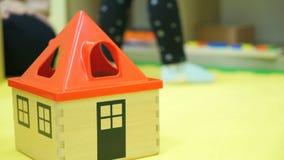 Los niños juegan la casa con el tejado rojo en el piso almacen de video