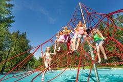 Los niños juguetones se sientan en cuerdas rojas del patio Imagenes de archivo