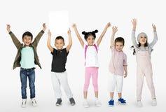 Los niños juntos muestran el retrato en blanco del estudio del espacio de la copia de papel imagen de archivo