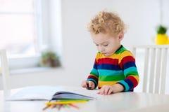 Los niños leen, escriben y pintan Niño que hace la preparación Foto de archivo