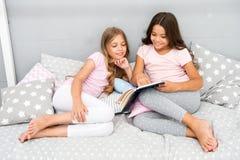 Los niños leyeron el libro en cama Los mejores amigos de las muchachas leyeron cuento de hadas antes de sueño Los mejores libros  imagen de archivo