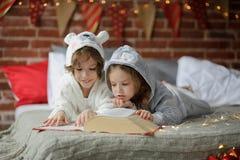 Los niños leyeron un gran libro con cuentos de la Navidad Fotos de archivo libres de regalías