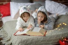 Los niños leyeron un gran libro con cuentos de la Navidad Foto de archivo libre de regalías