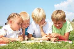 Los niños leyeron un libro Fotografía de archivo