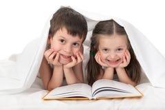Los niños leyeron un libro en cama Fotos de archivo