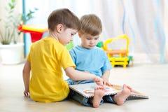 Los niños leyeron un libro que se sentaba en piso en casa Imagen de archivo