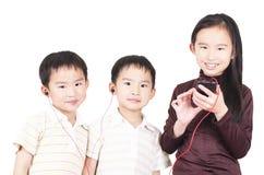 Los niños lindos escuchan la música Imagen de archivo
