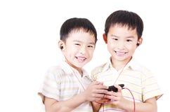 Los niños lindos escuchan la música Foto de archivo