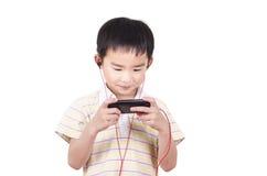 Los niños lindos escuchan la música Foto de archivo libre de regalías