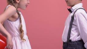 Los niños lindos juntan el cambio de los globos en forma de corazón, regalo de día de San Valentín, amor almacen de video