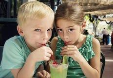 Los niños lindos que comparten una julepe de menta beben en un café Foto de archivo