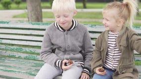 Los ni?os lindos se est?n sentando en un banco en el parque almacen de video