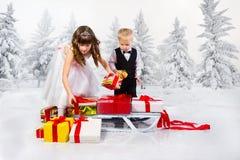 Los niños llevan un montón de regalos en un trineo fotografía de archivo