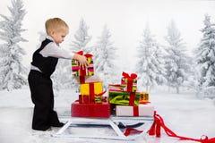 Los niños llevan un montón de regalos en un trineo fotos de archivo libres de regalías