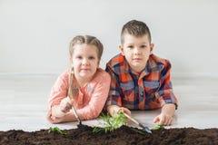 Los niños mienten en el piso y miran el símbolo de la plántula del Día de la Tierra Foto de archivo libre de regalías