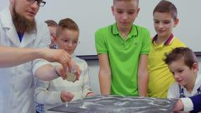 Los niños miran la arena del baile en la placa del chladni en laboratorio almacen de video