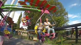 Los niños montan en un feliz paseo en el parque de atracciones Cámara lenta metrajes