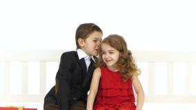 Los niños montan en un oscilación blanco se dicen secretos en el oído Fondo blanco almacen de video
