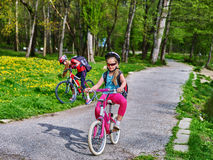Los niños montan la bicicleta en hierba verde y flores en parque Fotos de archivo libres de regalías