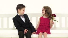 Los niños montan un oscilación y besos de un niño pequeño la muchacha en la mejilla Fondo blanco Cámara lenta metrajes