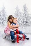 Los niños montan un trineo en la madera del invierno foto de archivo