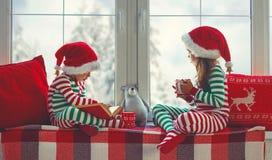 Los niños muchacha y muchacho en pijamas están tristes el mañana de la Navidad por la ventana imagen de archivo