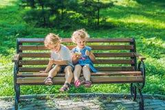 Los niños muchacho y muchacha que se sientan en un banco por el mar y comen una a Imagen de archivo libre de regalías