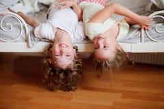Los niños, muchacho y muchacha, traviesos en la cama en el dormitorio fotos de archivo