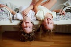 Los niños, muchacho y muchacha, traviesos en la cama en el dormitorio imagenes de archivo