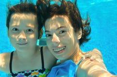 Los niños nadan en la piscina subacuática, haciendo el selfie, las muchachas activas felices se divierten, deporte de los niños Foto de archivo