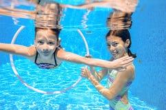 Los niños nadan en la piscina subacuática, las muchachas activas felices se divierten debajo del agua Imagenes de archivo