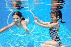 Los niños nadan en la piscina subacuática, las muchachas activas felices se divierten debajo del agua Imagen de archivo