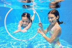 Los niños nadan en la piscina subacuática, las muchachas activas felices se divierten debajo del agua Foto de archivo
