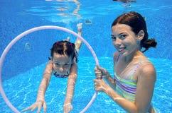 Los niños nadan en la piscina subacuática, las muchachas activas felices se divierten debajo del agua Foto de archivo libre de regalías